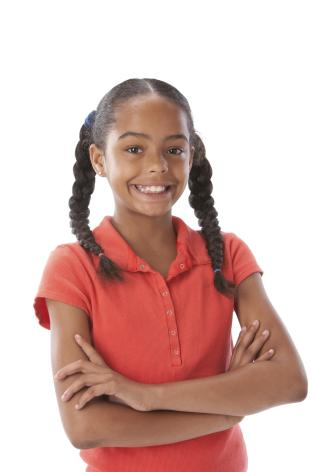 A head and shoulders image of a black little real girl with her arms crossed and a big smile on her face.