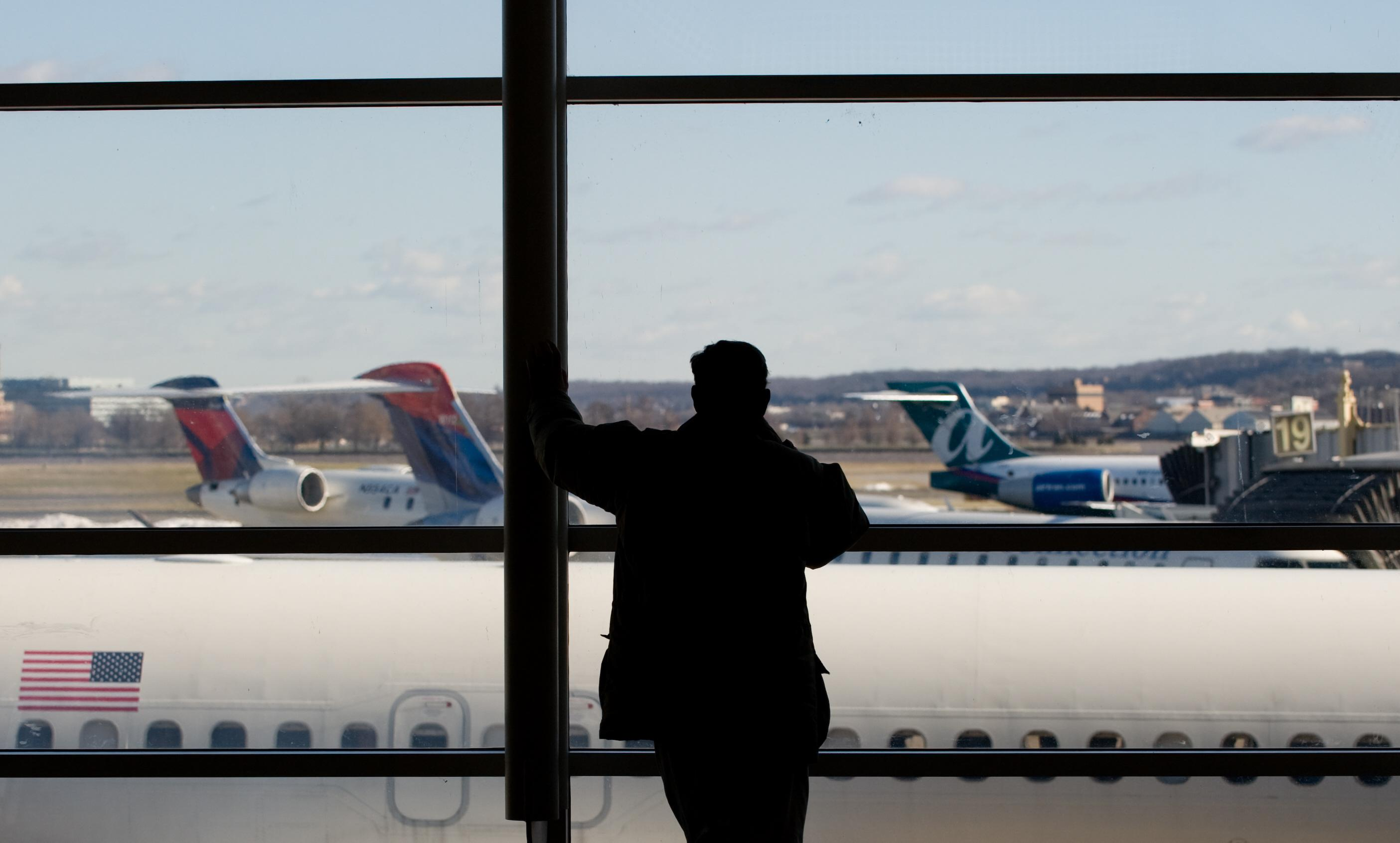 A man looks out the window at airplanes
