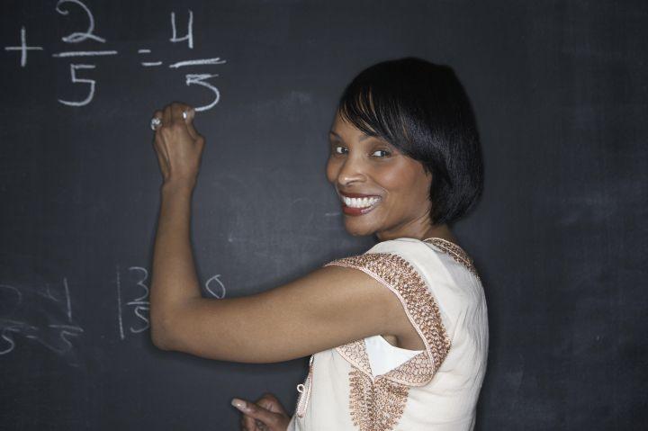 Teacher writing with chalk on a blackboard.