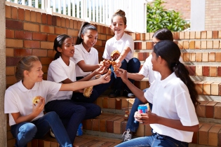 Female students having casual lunch at staircase