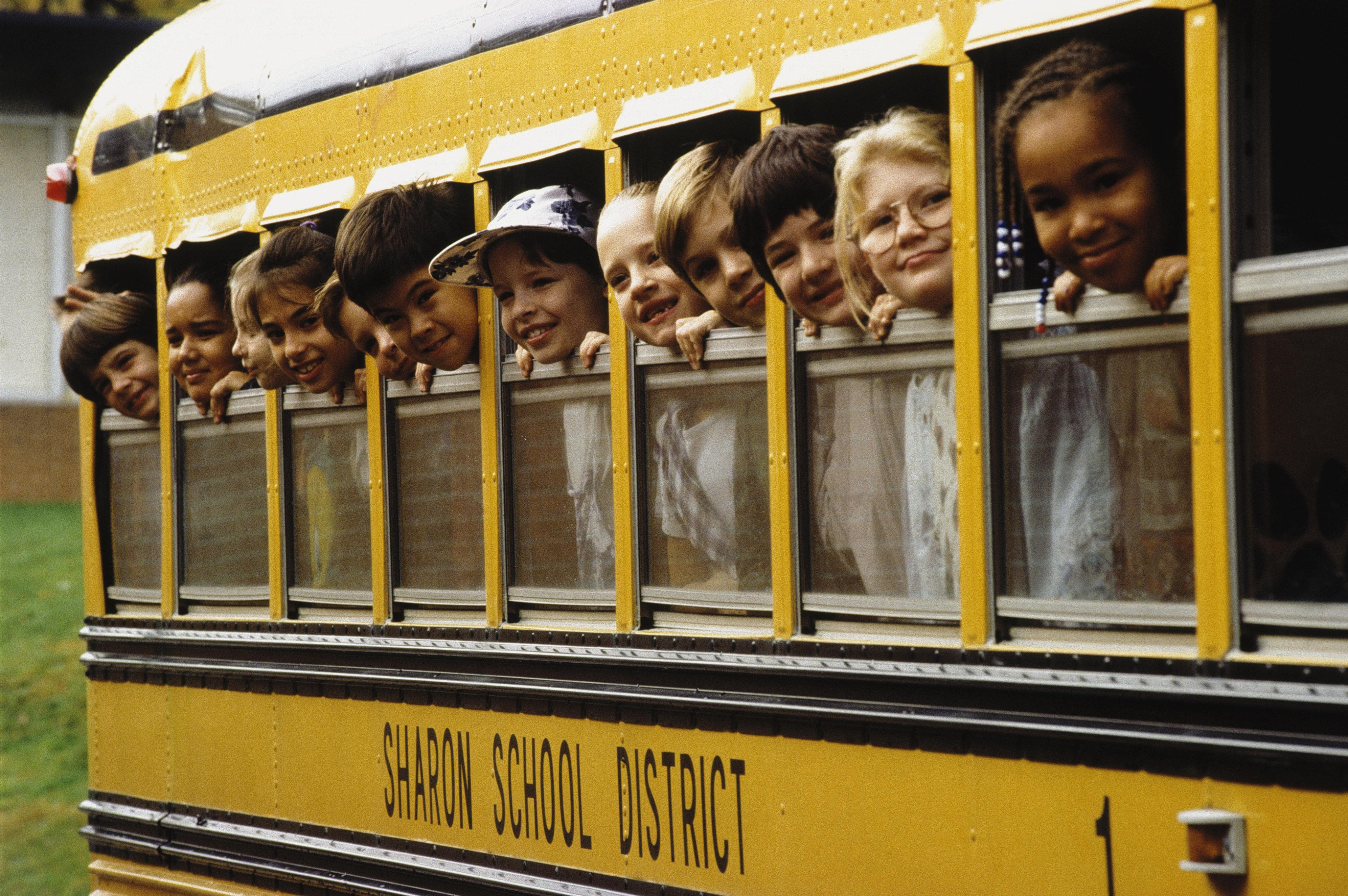 School children looking out school bus windows.