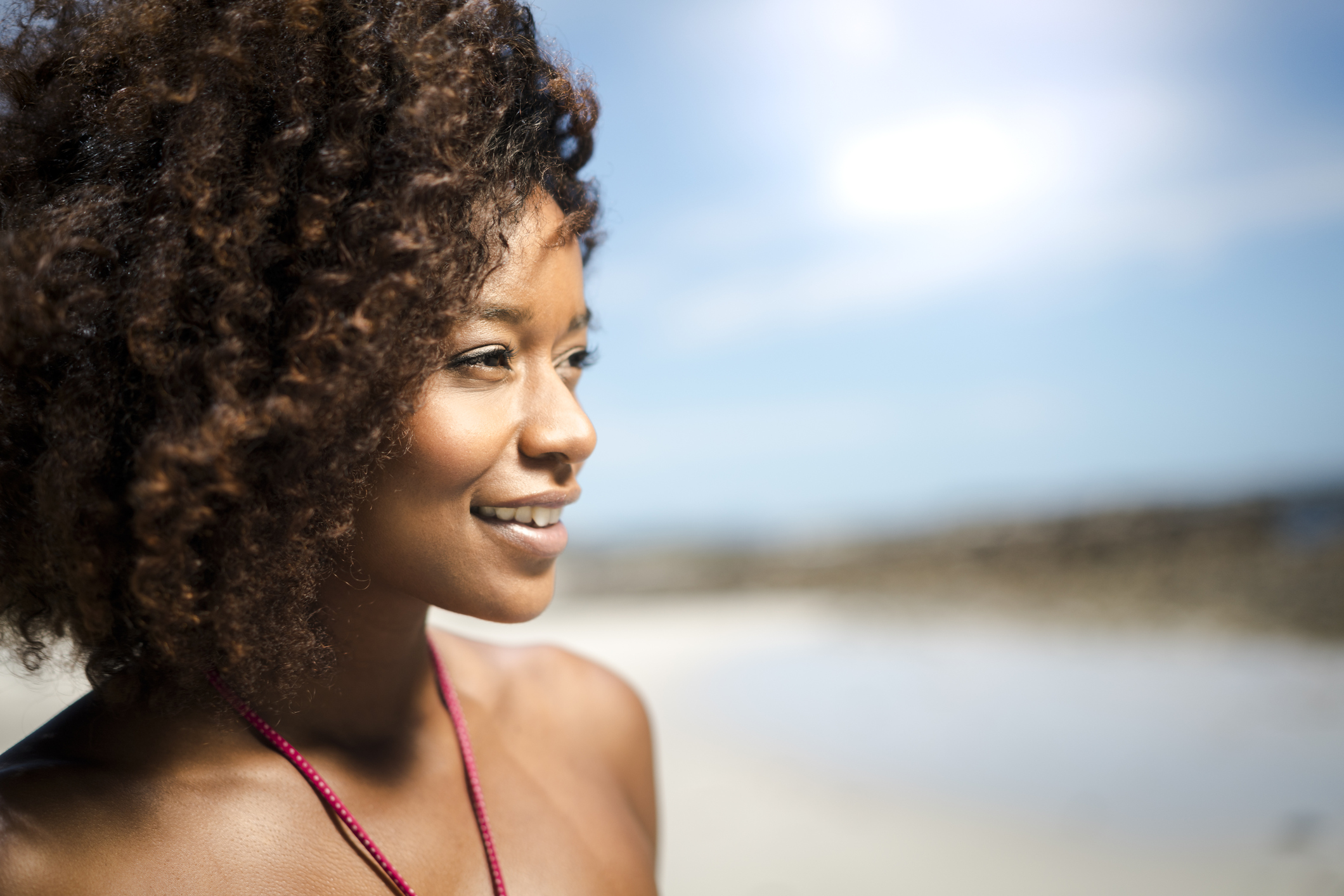 Close-up of thoughtful woman smiling at beach