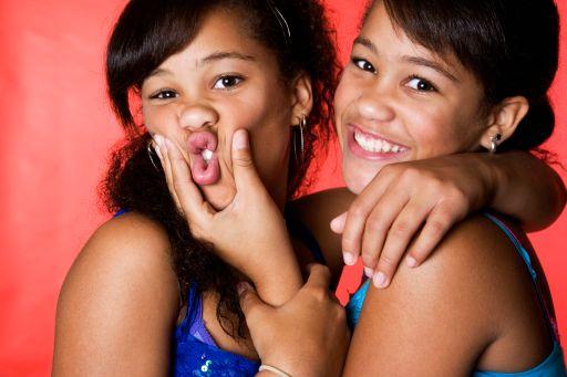 Mixed race teenage twin girls making faces