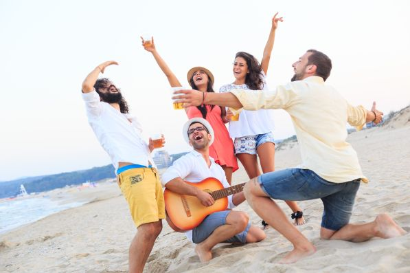 Friends celebrating and drinking beer on beach