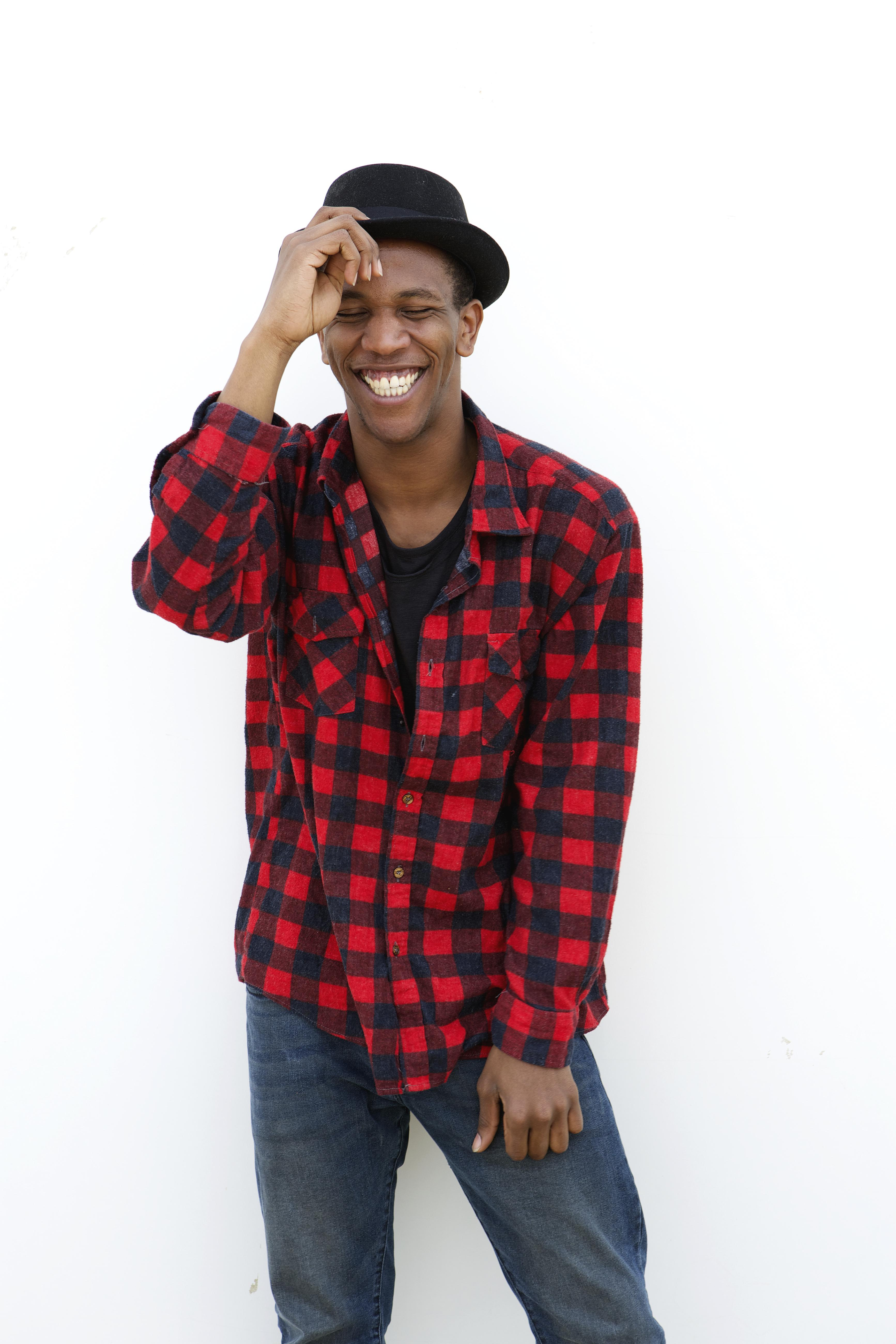 Portrait of a trendy young man laughing outdoors on white background