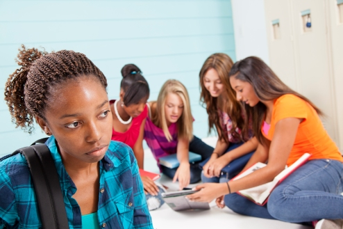 Teenage girls bully classmate. Gossip, talking. School hall. Lockers.