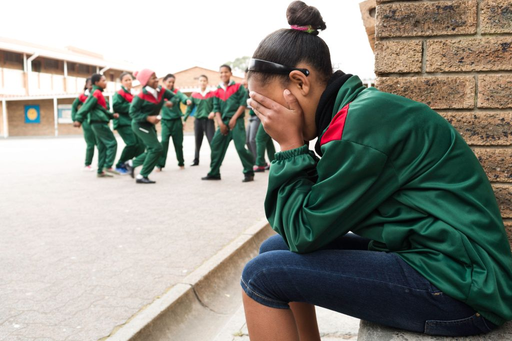 School girl cries as others laugh
