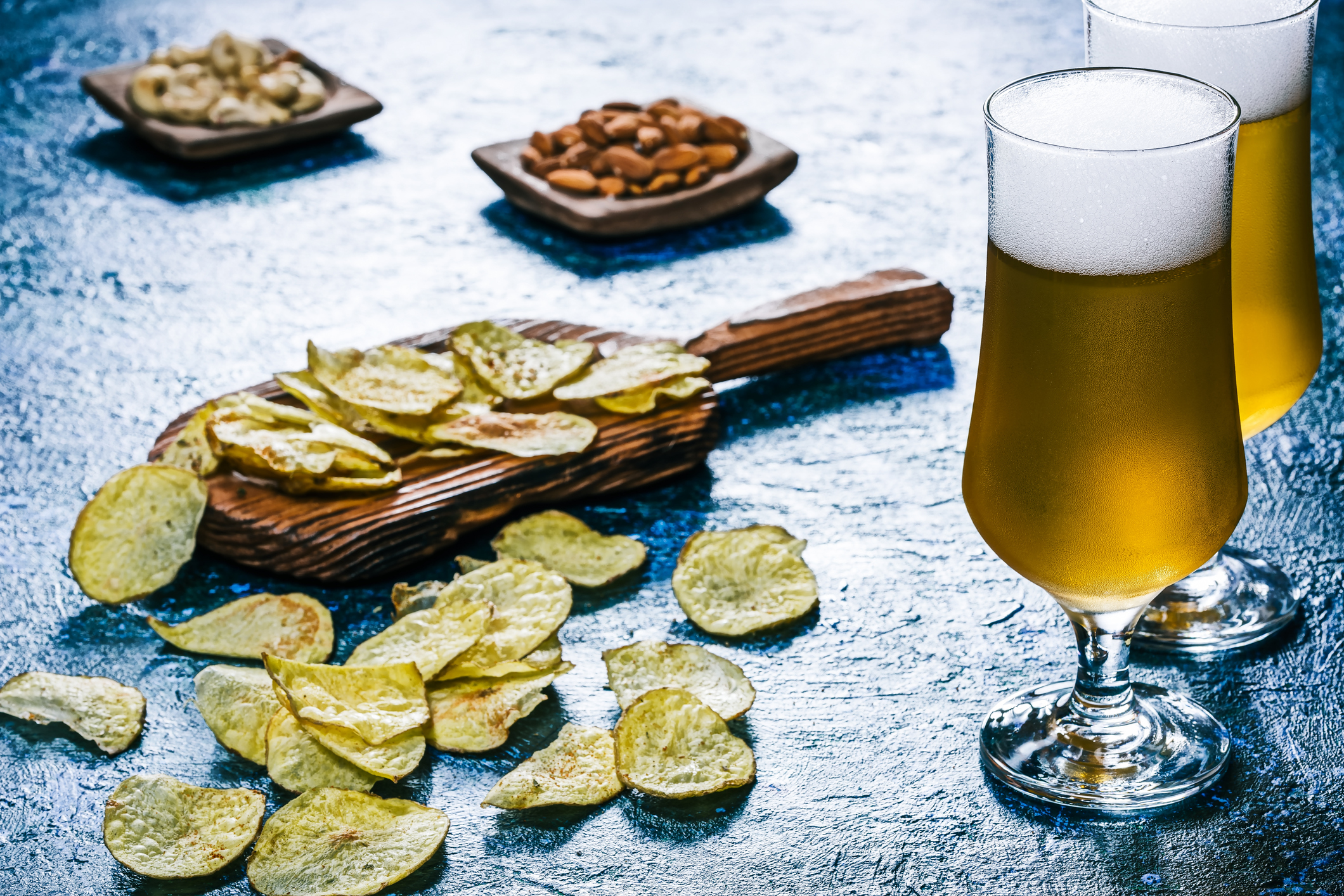 Beer and snack over glossy blue