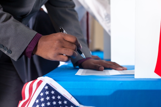 Man's hands while voting in election vote booth