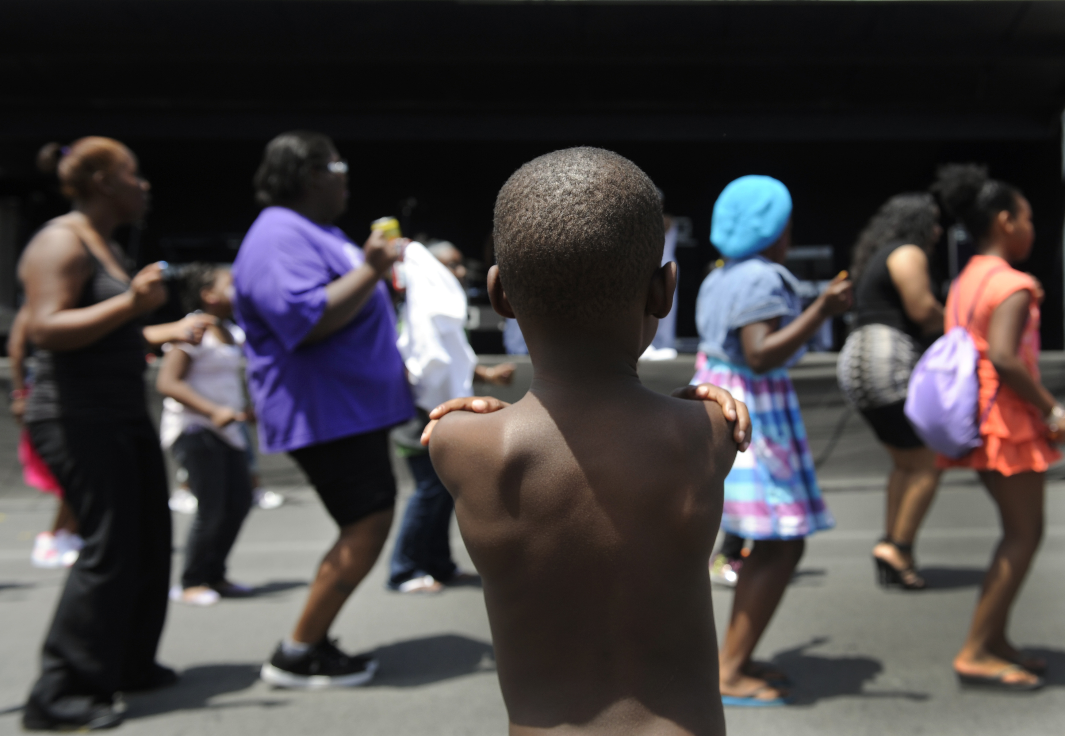 LaTrone Taylor-Witherspoon, 4, watches as a crowd gathers in front of the main stage at the festival to do the Cupid Shuffle. The Friends of Blair Caldwell African American Research Library Foundation hosts the 2011 Denver Juneteenth Celebration: We Defin