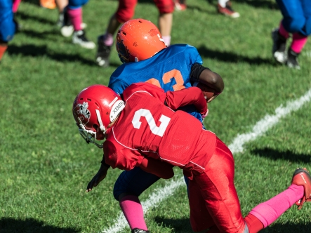 Making a tackle during a Pop Warner football game...
