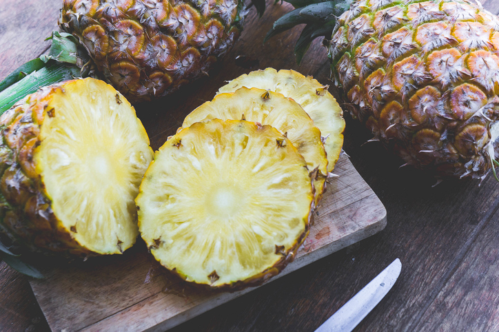 Close-Up Of Pineapples On Cutting Board