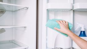 Cropped Hands Of Woman Cleaning Fridge At Home