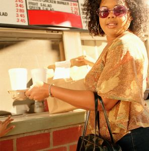 Woman picking up order from window of fast food restaurant