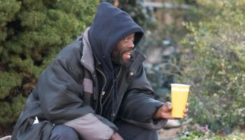 A homeless man begs for money in downtow...